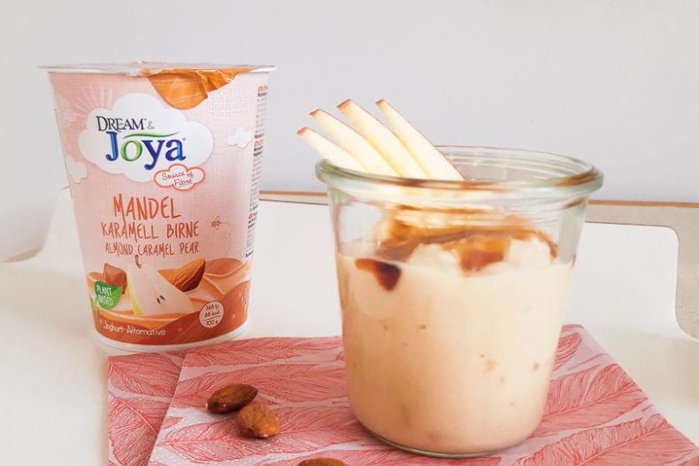 Dream & Joya Mandel Joghurtalternative Karamell Birne - Ein Becher Dream & Joya Mandel Joghurtalternative Karamell Birne und Mandeln auf einem weißen Tablett - © Joya