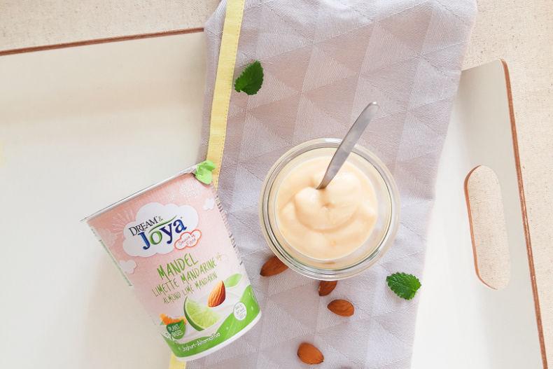 Dream & Joya Mandel Joghurtalternative Limette Mandarine - Ein Becher Dream & Joya Mandel Joghurtalternative Limette Mandarine und Mandeln auf einem weißen Tablett - © Joya