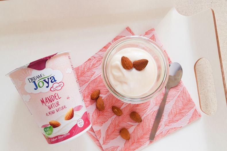 Dream & Joya Mandel Joghurtalternative Natur - Ein Becher Dream & Joya Mandel Joghurtalternative Natur und Mandeln auf einem weißen Tablett - © Joya