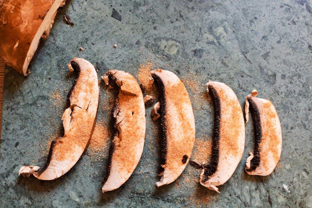 Ceasar Salad Zubereitung - Geschnittener Portobello Pilz mit Brathuhngewürz auf grauer Steinplatte.