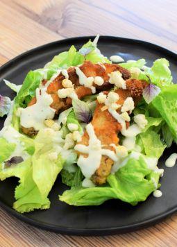 Ceasar Salad - Caesar Salad auf einem Schwarzen Teller auf braunem Holztisch