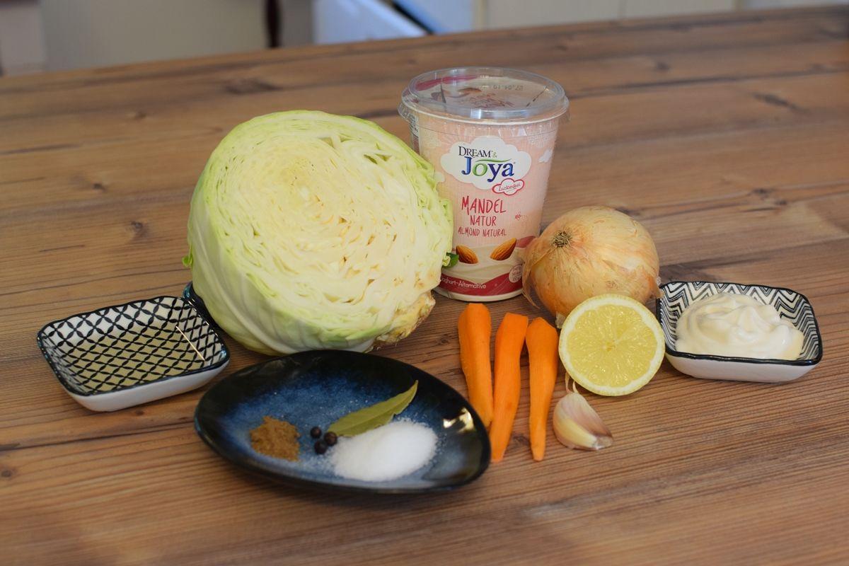 Coleslaw Zutaten - Weißkraut, Karotten, Knollensellerie auf braunem Holztisch