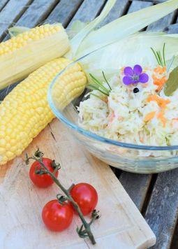 Coleslaw  - Eine Glasschüssel mit Coleslaw mit zwei Maiskolben auf Holztisch