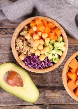 Buddha Bowls - Verschieden Buddha Bowls mit einer halben Avocado auf einem Holztisch