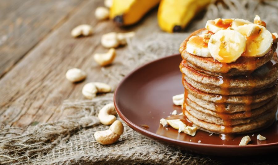 Mandel-Hafer Pancakes  - A stack of oat pancakes with bananas and nuts on a brown plate