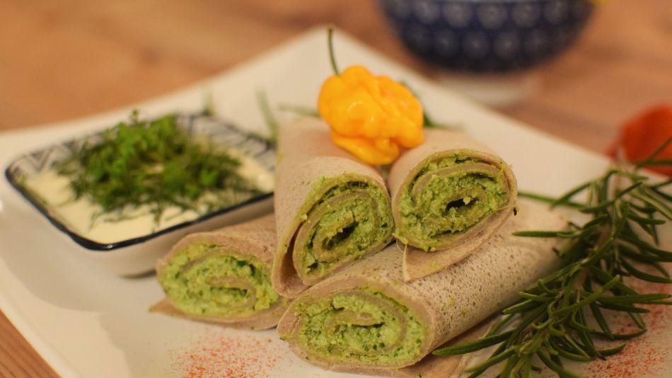 Buchweizenröllchen mit Grünkohl-Walnuss Pesto - Vier aufgeschnittene Buchweizenröllchen mit grüner Füllung auf einem weißen Teller