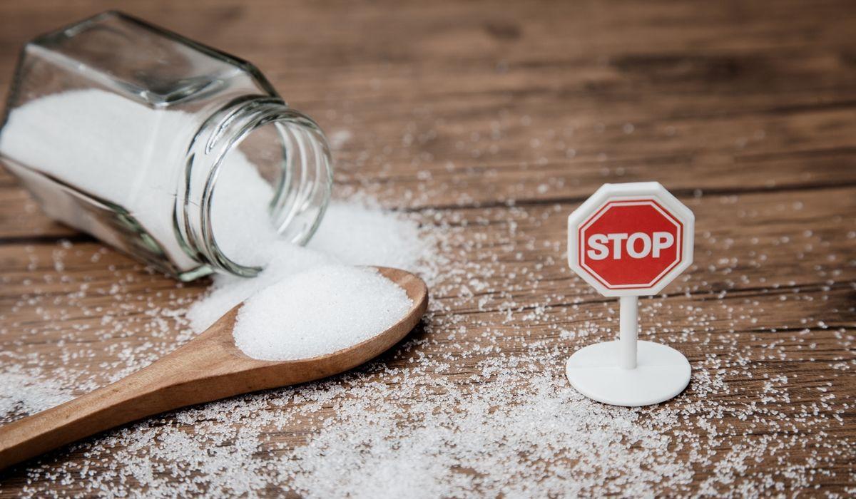 7-Tipps-wie-du-deinen-Zuckerkonsum-reduzierst - Ein Glas mit weißem Zucker und einem Stopschild auf einem Holztisch