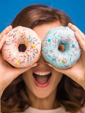 Warum-du-auf-deinen-Zuckerkonsum-achten-solltest_1200x830 - Eine lachende Frau die sich Donuts vor die Augen hält