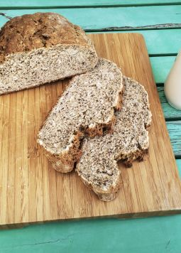 Kornbrot mit Chiasamen  - Grain bread with chia seeds cut open on a wooden board with a glass of vegetable milk