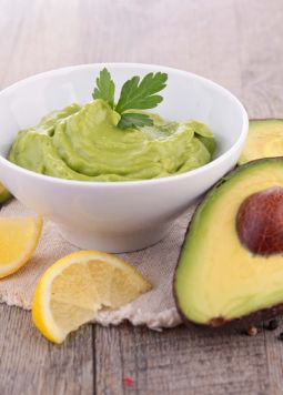 Avocado Dip - A white cup with avocado dip on a wooden table