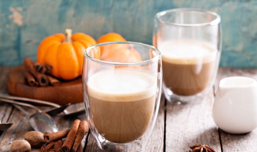 Vegan Pumpkin Spice Latte - Zwei Gläser mit Pumpkin Spice Latte auf einem Holztisch mit Gewürzen und Kürbissen