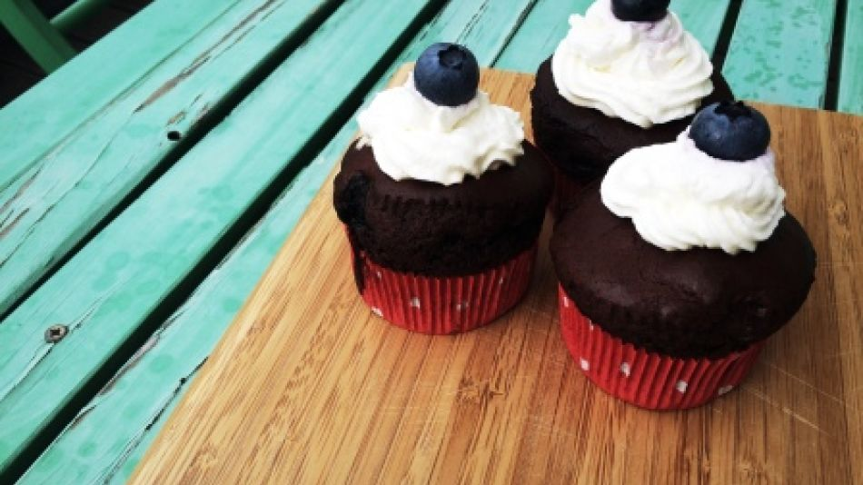 Vegane Schoko-Heidelbeer Cupcakes  - Three chocolate cupcakes with cream and a blueberry on a wooden board