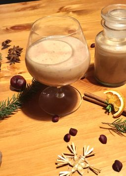 Veganer Lebkuchenlikör - A glass with gingerbread liqueur and Christmas decoration on a wooden table