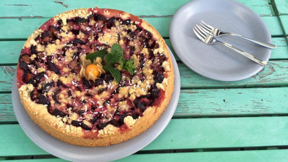 Veganer Zwetschkenkuchen - Round plum cake with sprinkles on a turquoise wooden table