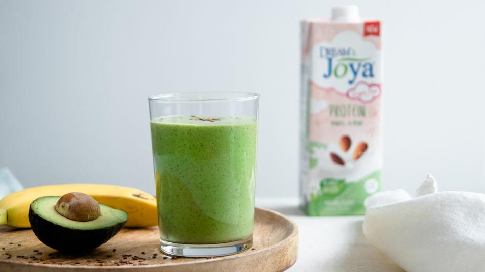 Green Protein Smoothie - Glas mit grünem Smoothie, daneben Avocado und Banane und der Mandel Drink Protein