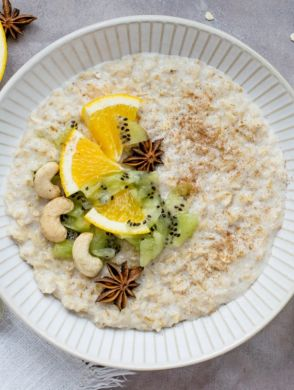 Porridge-im-Winter(c)monika-grabkowska-325047 - Eine weiße Schüssel mit Porridge, darauf sind Kiwis, Orangen und Cashewnüsse - © Unsplash monika-grabkowska-325047
