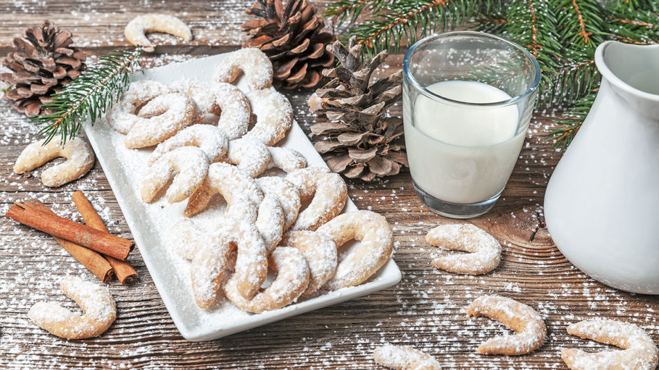 Vanillekipferl - Crescent shaped vanilla baked goods on a plate with a glass full of plant based milk on a christmassy decorated table