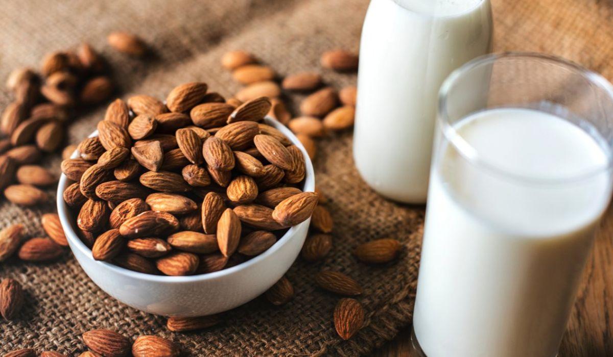 Mandeln und pflanzliche Milchalternative - Eine Schüssel voller Mandeln steht auf einem Holztisch neben einem Glas pflanzlicher Milchalternative