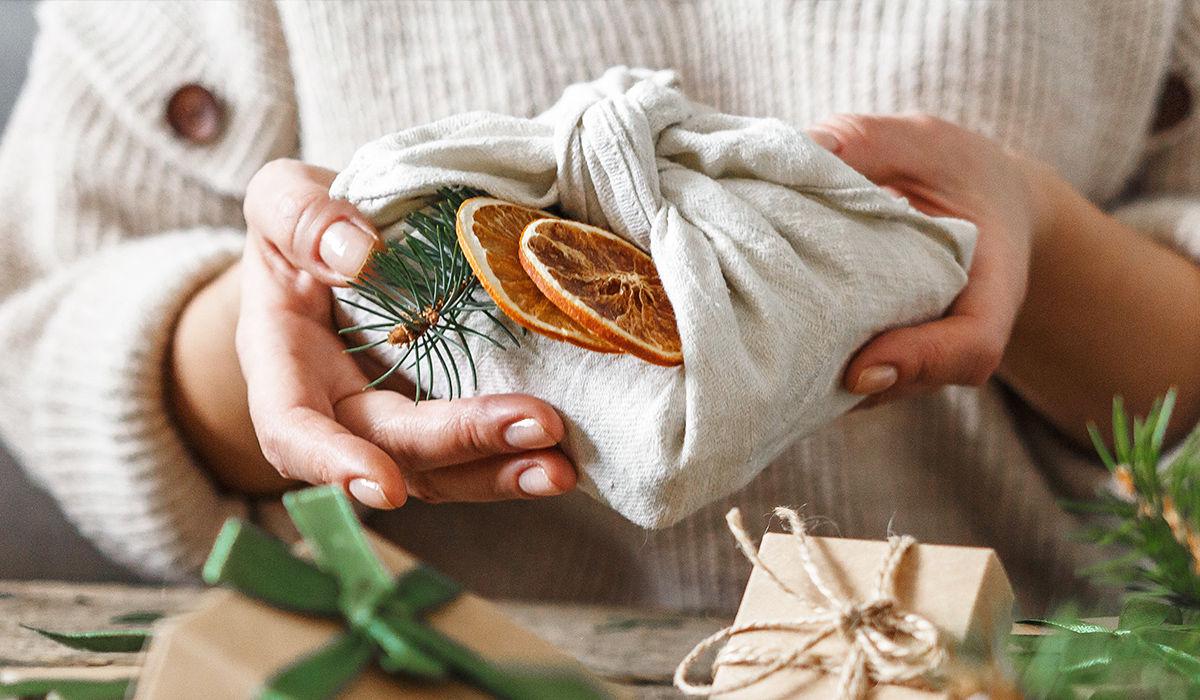 Nachhaltige Weihnachten - Frau übergibt Geschenk, das in Stoff eingepackt und mit einem Tannenzwei und getrockneten Orangenscheiben dekoriert ist.