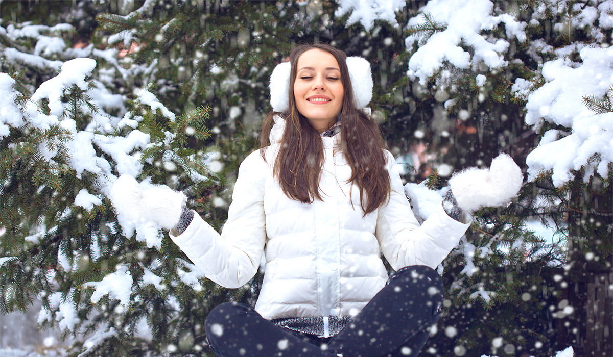 Ausgeglichene Weihnachten - Woman sitting cross-legged in the snow, her hands in a meditation pose, enjoying the falling snow and winter