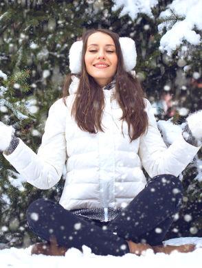 Ausgeglichene Weihnachten - Frau sitzt mit überkreuzten Beinen im Schnee, Hände in Meditationshaltung, und genießt den Winter