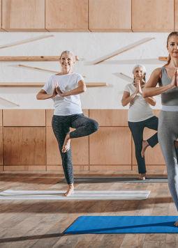 Neujahrsvorsatz: Balance Yoga - Szene im Yoga Studio, fünf Menschen stehen in der Baum Pose
