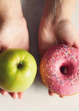 Balance beim Essen - 2 Hände auf hellem Hintergrund, eine hält einen Apfel, die andere ein Donut mit rosa Zuckerglasur