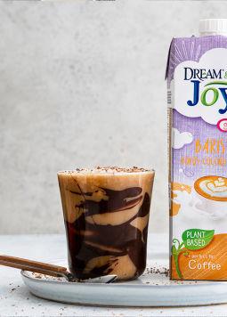 DJ_Iced-Choc-Frappe-mit-Pack_1200x800px.jpg - Ein Glas schokoladiges Eiskaffe Frappe mit einer Packung Dream & Joya Kokos Drink Barista vor weißem Hintergrund.