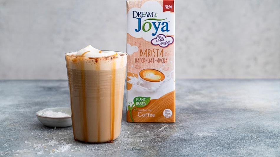 DJ_Salted-Caramel-Latte-mit-Pack_1200x800px.jpg - Ein Glas mit Salted Caramel Latte und einer Packung Dream & Joya Barista Hafer auf einem grauen Tisch und vor grauem Hintergrund.