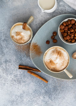 DJ_Zimt-Haselnuss-Cappuccino-mit-Pack_1200x800px.jpg - Two cups of cinnamon hazelnut cappuccino on a blue plate with a bowl of hazelnuts, cinnamon sticks, white cloth and a pack of Dream & Joya Barista Soy Drink on a gray background.