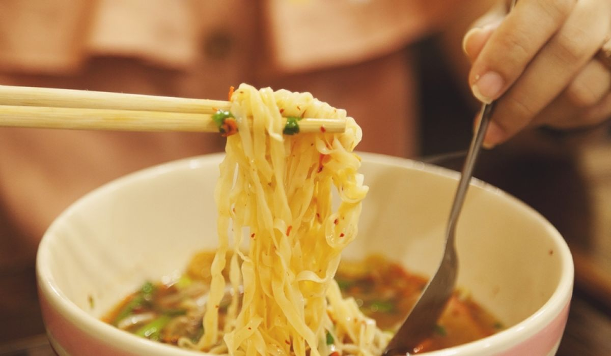 One Pot Thai-Tagliatelle mit Cashewkernen - Eine Frau isst das One Pot Gericht Thai-Tagliatelle mit Cashewkernen mit Stäbchen