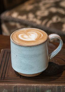 Kaffeehausklassiker - Keramik-Tasse mit Kaffee und Latte Art Heart in einem Kaffeehaus
