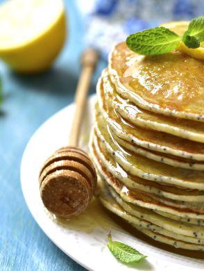 Mohn-Zitronen Pancakes - Ein Stapel Mohn-Zitronen-Pancakes mit Sirup und einer Zitronenscheibe auf einem weißen Teller