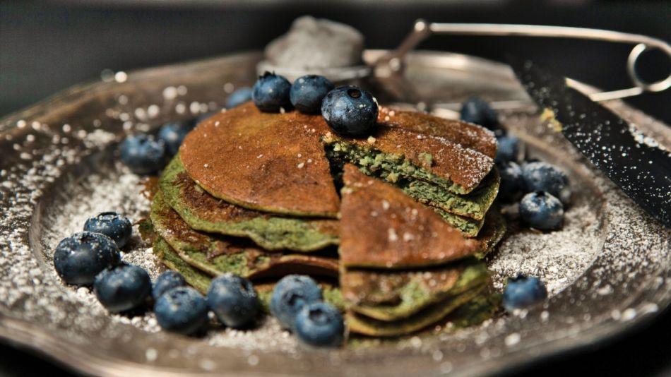 Joya & SPIRULIX Green Pancakes  - Drei grüne Spirulina Pancakes mit Heidelbeeren auf einem Metallteller. - © Spirulix