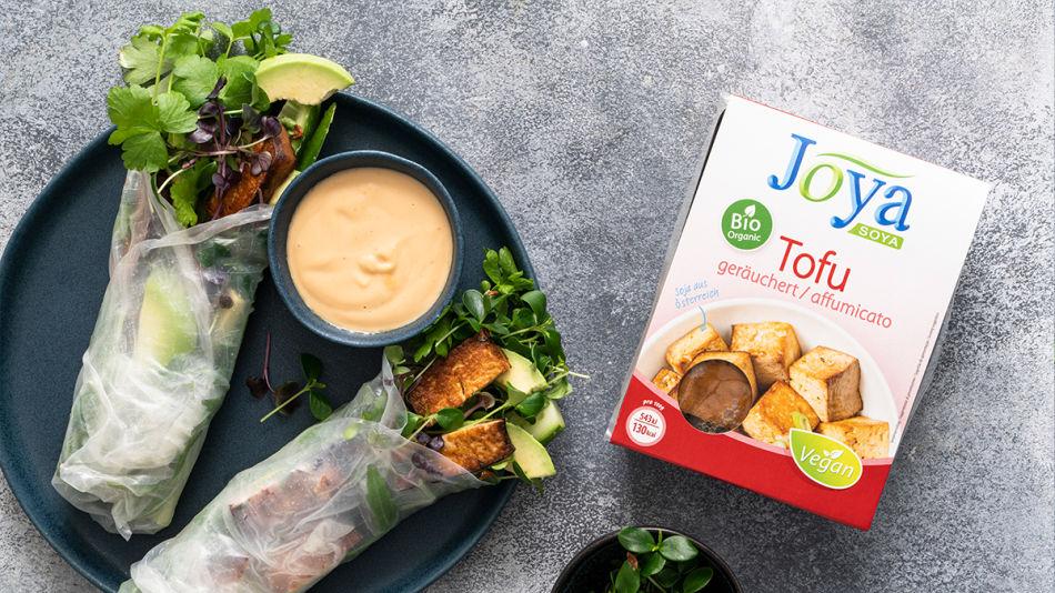 Reispapier Rollen mit knusprigem Tofu und Erdnusssauce - Auf einem dunklen Teller liegen zwei Reispapier Rollen, gefüllt mit Tofu, grünem Blattgemüse, Sprossen und Kräutern. Daneben steht eine kleine Schüssel mit Erdnusssauce und der Joya Bio Tofu geräuchert.