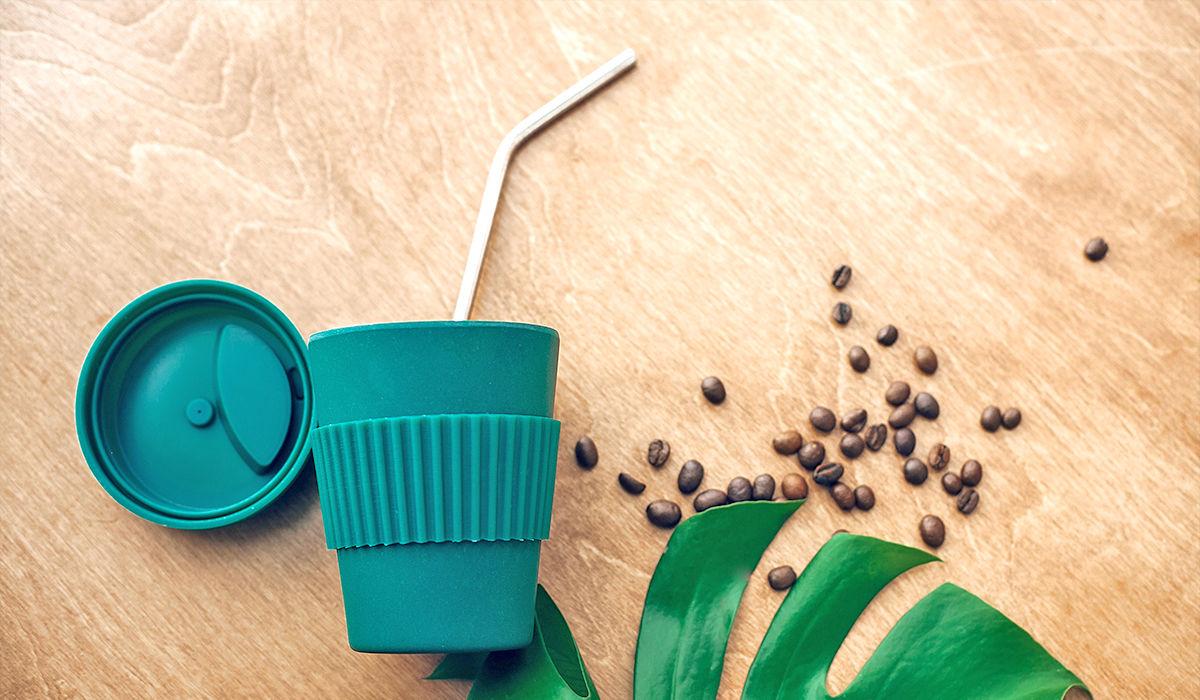 Nachhaltiger Kaffeekonsum - Grüner Mehrwegbecher mit Metall-Strohalm auf Holztisch, mit ein paar Kaffeebohnen und einem Blatt