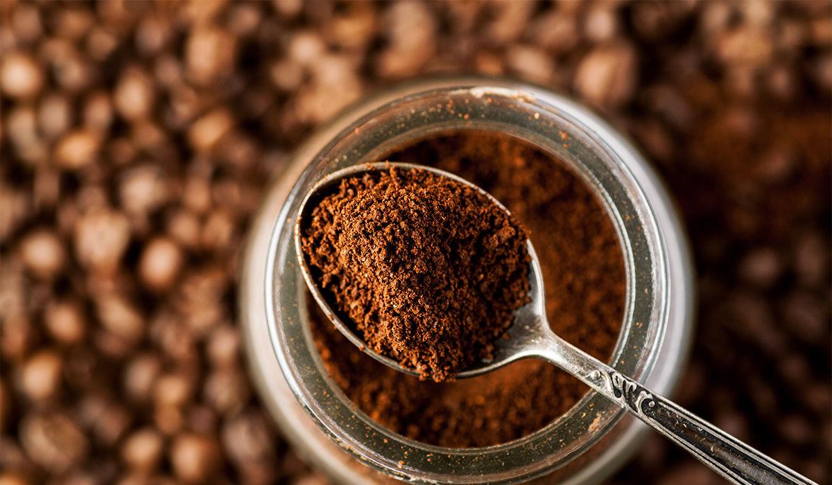 8 Arten, um Kaffeesatz wiederzuverwenden - A spoonful of coffee powder lies on a glass with coffee powder, coffee beans can be seen in the background