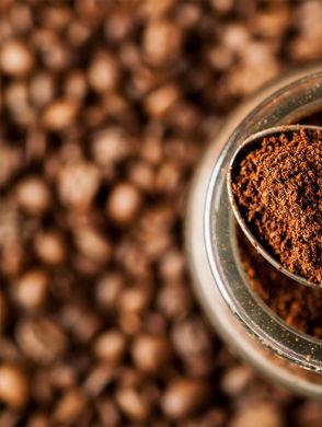 8 Arten, um Kaffeesatz wiederzuverwenden - Ein Löffel mit Kaffeepulver liegt auf einem Glas mit Kaffeepulver, im Hintergrund sind Kaffeebohnen erkennbar
