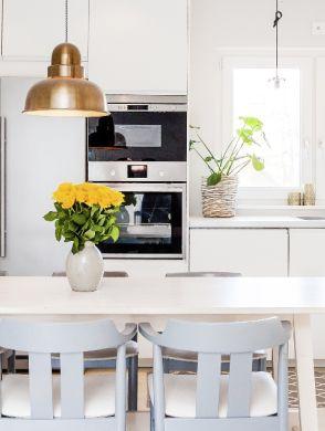 Frühjahrsputz in der Küche - Eine weiß eingerichtete Küche mit Esstisch, darauf steht ein gelber Blumenstrauß - © Joya
