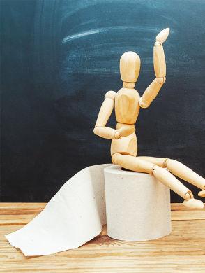 JO_Blog-Darm-Immunsystem - Eine Holzfigur sitzend auf einer Rolle Toilettenpapier vor einem schwarzen Hintergrund und auf einem Holztisch.