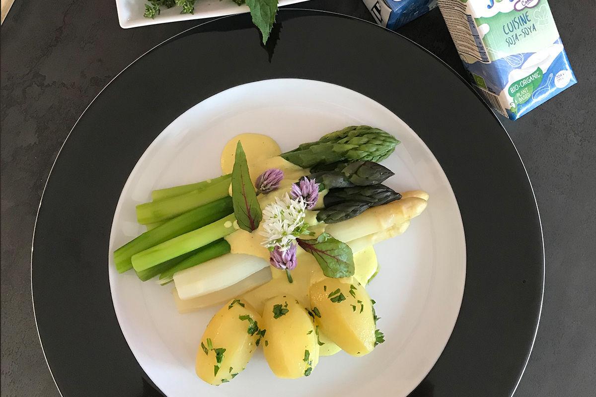 Spargel Hollandaise mit Packshot - Draufsicht auf einen weißen Teller mit breitem, schwarzem Rand. Auf dem Teller ist grüner und weißer Spargel angerichtet mit Petersilerdäpfeln und Sauce Hollandaise. Daneben sieht man Packungen der Soja Cuisine