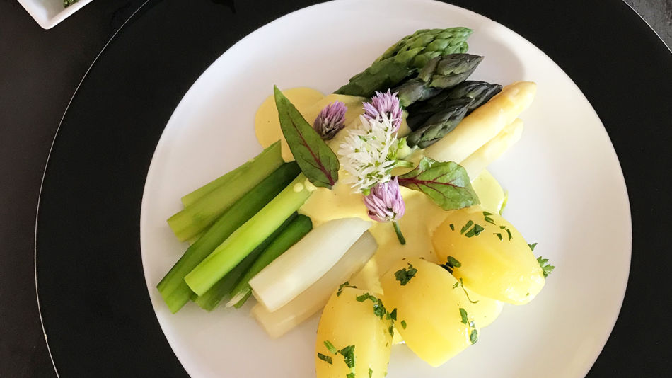 Spargel Hollandaise - Draufsicht auf einen weißen Teller mit breitem, schwarzem Rand. Auf dem Teller ist grüner und weißer Spargel angerichtet mit Petersilerdäpfeln und Sauce Hollandaise