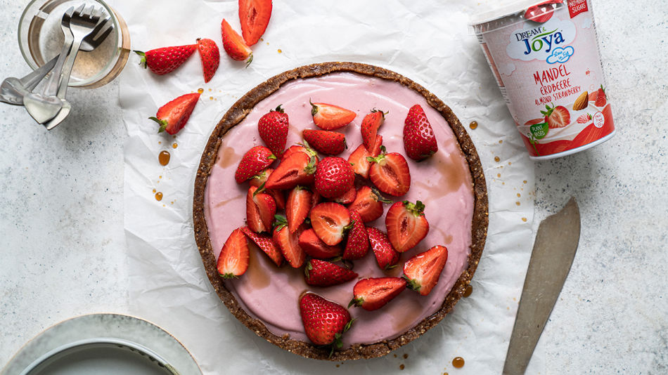 Strawberry Yogurt Tarte - Strawberry Yogurt Tarte with freh strawberries next to a package of Dream & Joya Almond with Yogurt Cultures Strawberry on a layer of baking paper.
