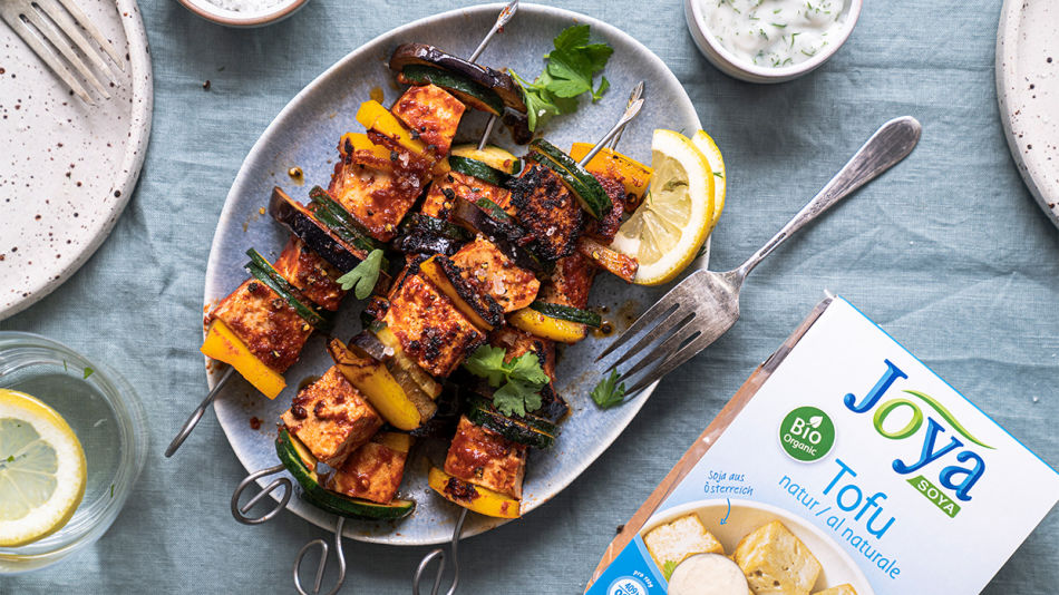 Tofu Skewers - Four pieces of BBQ skewers with a lemon and a fork on a grey plate next to a package of Joya Organic Tofu natur.