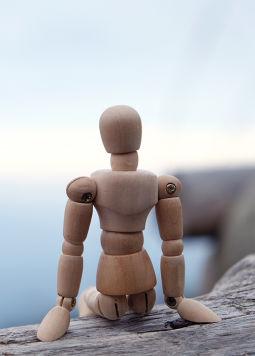 Darmgesundheit Teil 2 - Gutes Bauchgefühl - Eine Holzfigur sitzt entspannt am Rand einer Klippe und blickt aufs offene Meer hinaus - © shutterstock