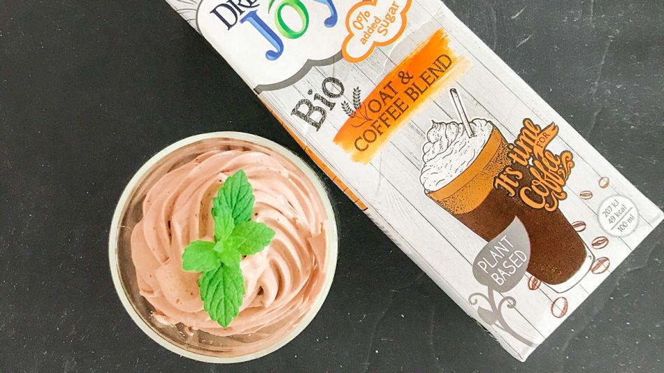 Kroepfl-Kaffee-Schoko-Mousse - Ein Glas mit Kroepfls Kaffee SChoko Mousse dekoriert mit Minze neben einer Packung Dream & Joya Hafer Kaffee auf grauem Hintergrund.