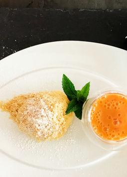 Kroepfl-Marillenknoedel - Ein Kroepfl Marillenknoedl mit einem Schüsselchen Marillenschaum angerichtet auf einem weißen Teller, neben einer PackungDream & Joya Kokos mit Joghurtkulturen auf grauem Hintergrund.