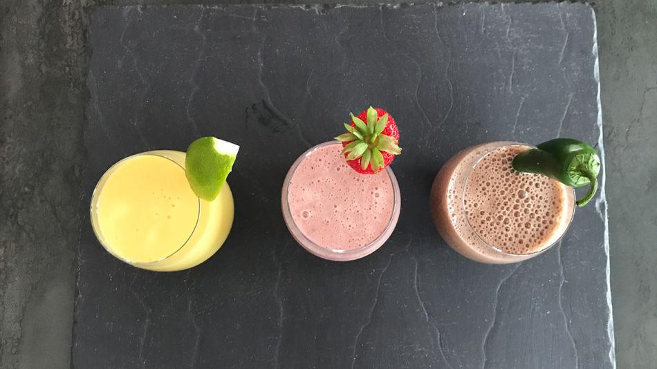 Kroepfl-Sommer-Drinks - Drei Gläser gefüllt mit Kroepfls Sommer Drinks, Mandel-Mango-Limette, Schoko-Chili-Banane und Erdbeer-Minze-Basilikum auf einem grauen Steinbrett.