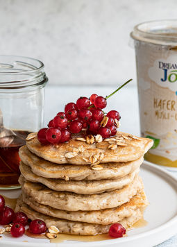 Hafer Müsli Pancakes - There is a stack of golden-brown pancakes on a plate with maple syrup on top and a few fresh currants next to it. In the background you can see a cup of Dream & Joya oats with yoghurt cultures muesli
