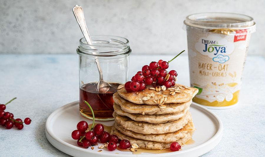 Hafer Müsli Pancakes - Auf einem Teller befindet sich ein Stapel goldbrauner Pancakes, darauf ist Ahornsirup und daneben ein paar frische Ribiseln. Im HIntergrund sieht man einen Becher vom Dream & Joya Hafer mit Joghurtkulturen Müsli